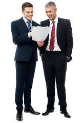 Businessmen evaluating deal documents