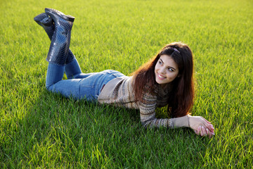 Portrait of a happy woman lying on the lawn