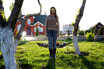 Full-length portrait of a young woman standing in garden