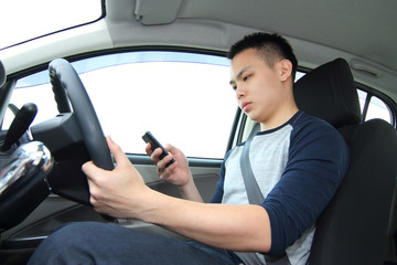 A male driver texting on a cellphone while driving
