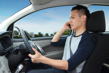 A man driving while talking on a cellphone