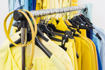 Closeup on yellow and blue color coordinated clothes on hangers.