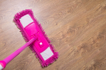 cleaning wooden parquet floor with pink mop