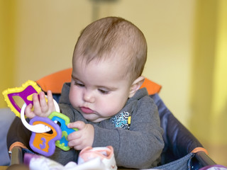 very focused baby girl playing with her ​​toy