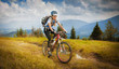 Woman mountain-bike riding on ridge with Carpatian Mountains - 64318058