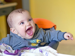 happy smiling baby sitting on  high chair