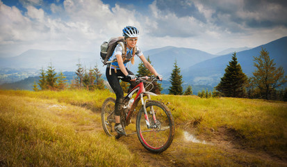 Woman mountain-bike riding on ridge with Carpatian Mountains