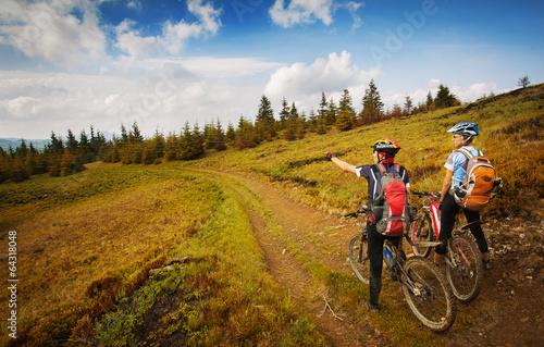 Zdjęcia na płótnie, fototapety, obrazy : Two young bikers looking at the mountains