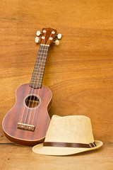 The ukulele and a hat is placed on a wooden floor.