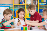 Fototapety Cute children drawing with colorful paints at kindergarten