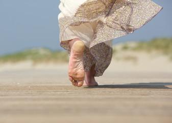 Female feet walking away at the beach