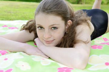 Teenager in Badeanzug liegt auf Decke
