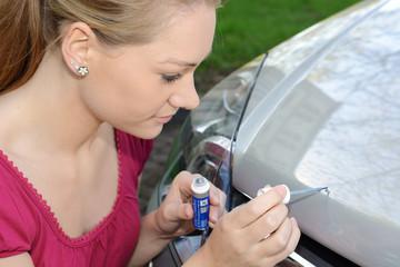 Frau bessert Lack-Schaden an Auto aus