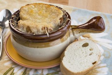 Traditional crock full of French Onion Soup with melted Gruyere