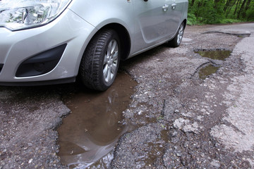 Damaged road full of cracked potholes in pavement