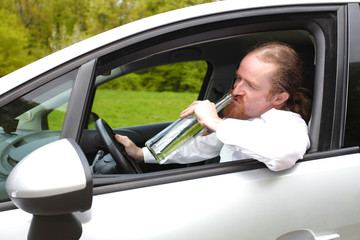 Drunk man in car with a bottle alcohol