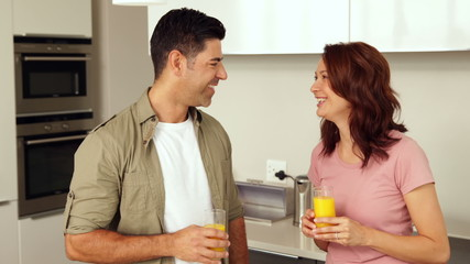 Couple chatting and drinking orange juice