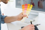Designer working with digitizer holding colour chart at his desk