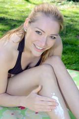 Twen in Bikini trägt Sonnencreme auf