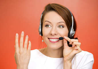 Happy smiling female help desk operator on a phone with customer