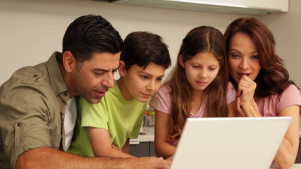 Parents using laptop with their cute children