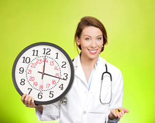 Time for your meds. Doctor holding wall clock and pills