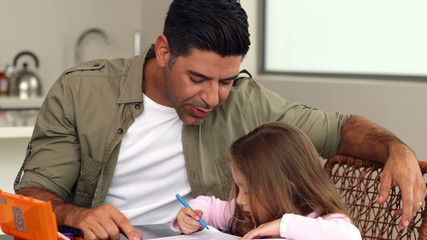 Little girl drawing at the kitchen table with her father