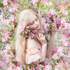 Beautiful woman and flowering tree. Beauty young girl in garden.