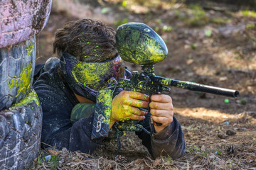 Paintball player in bright paint splashes