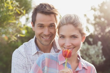 Smiling couple holding a flower in park
