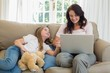 Woman using laptop by daughter on sofa