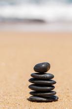 De stenen van Zen JY op het zandstrand in de buurt van de zee.