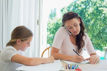 Woman using mobile phone while daughter studying at table
