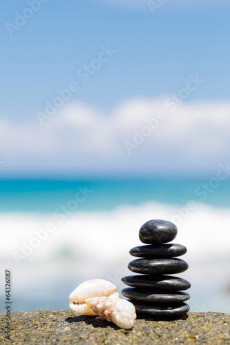 Juliste Zen stones jy on the sandy beach near the sea.