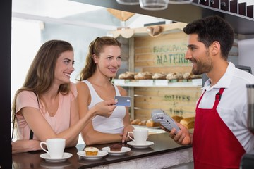 Friends with woman holding out credit card at coffee shop
