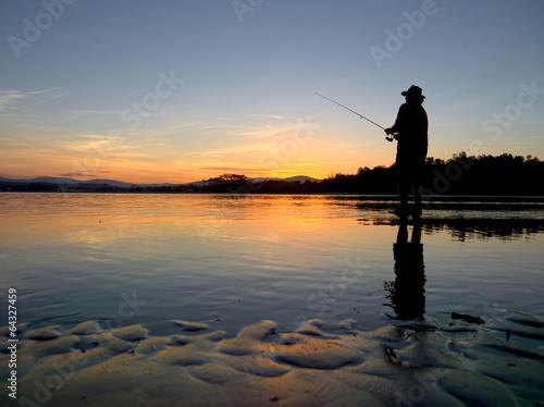 Fotobehang Vissen man fishing at sunset in bate mans bay