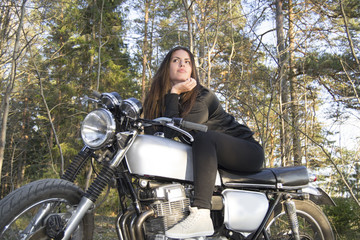 Sexy latina woman on a motorcycle posing in a forest