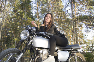 Sexy brunette woman on a motorcycle posing in a forest