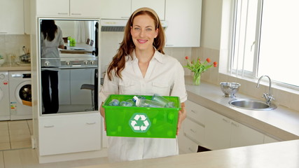 Beautiful brunette showing her box of recyclable materials