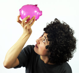 Young woman checks empty piggy bank
