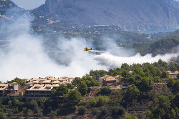 Plane in a fire burning mountain forest and village, danger for