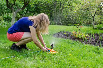 girl turns garden watering at  flower seedling