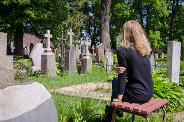 Sorrow woman near father husband tomb in cemetery