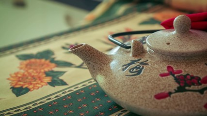 Zoom out shot of Asian Teapot on a colorful tablecloth