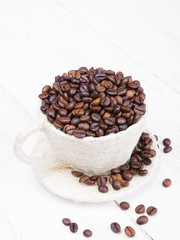 cup full of coffee beans on a white wooden background