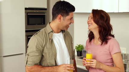 Young couple chatting and drinking orange juice
