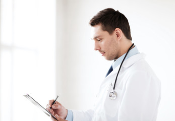 male doctor with stethoscope writing prescription