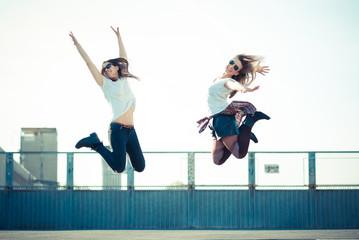 two beautiful young women jumping and dancing