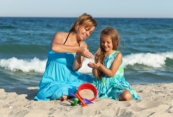 Woman and little girl on the beach