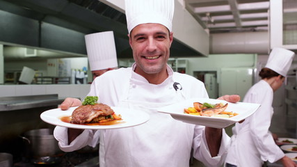 Smiling handsome chef showing two dishes to camera